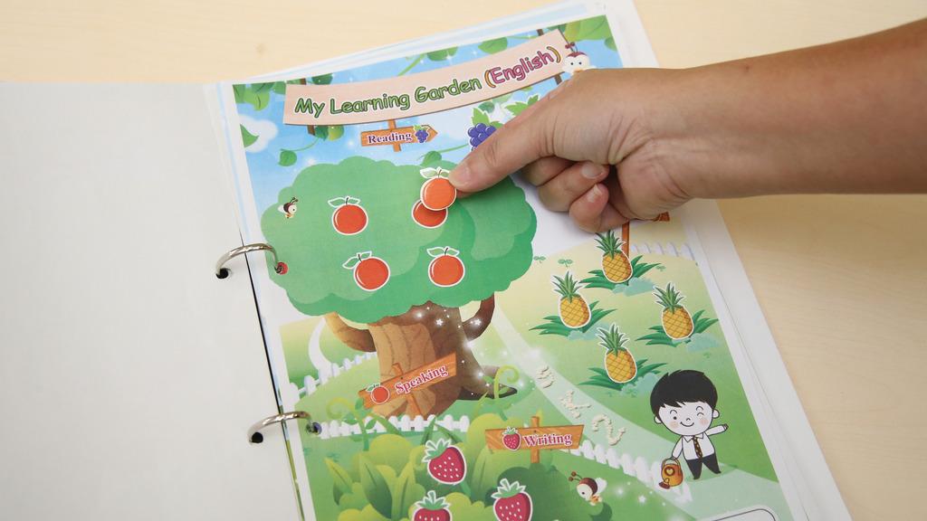 中英文科成績表是一張果園圖,4種水果代表聽、說、讀、寫能力,學生愈多該水果貼紙表示表現愈好。(曾有為攝)