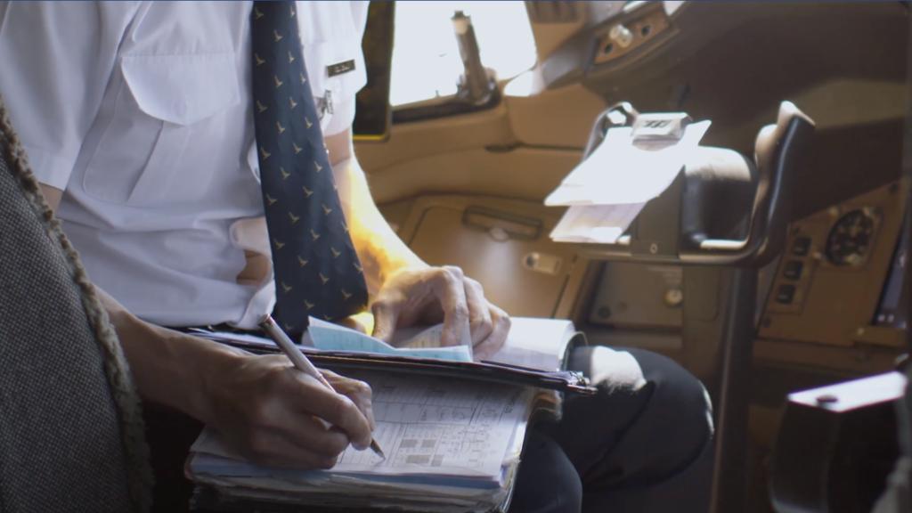 每次降落後,需要在飛行記錄簿中,記錄航班時間、起飛及降落時間、以及航班發生的事。(國泰視頻截圖)