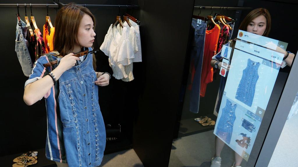阿里巴巴早前在香港推出人工智能時尚服飾概念店,消費者在店內拿起衣服,屏幕便能感應商品信息,及提供時尚選擇。(圖片來源:新華社)